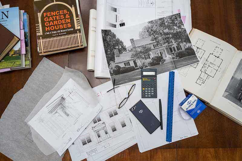 Architecture book, sketches, glasses, a pen and ruler, and other items lay on a wooden desk.