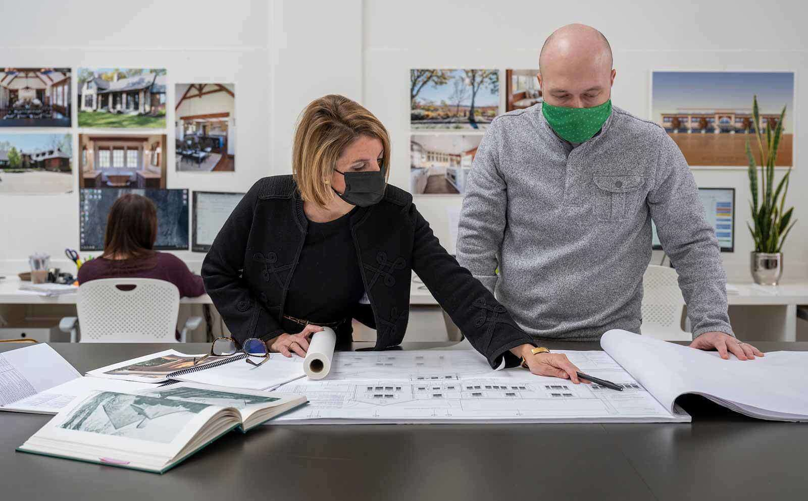 Two masked people stand at a desk looking at architecture sketches.