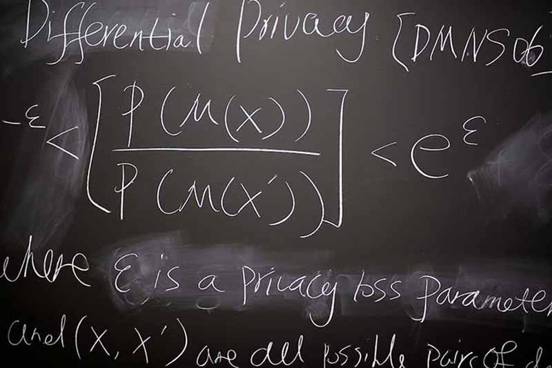 A black board with words and equations written in white chalk.
